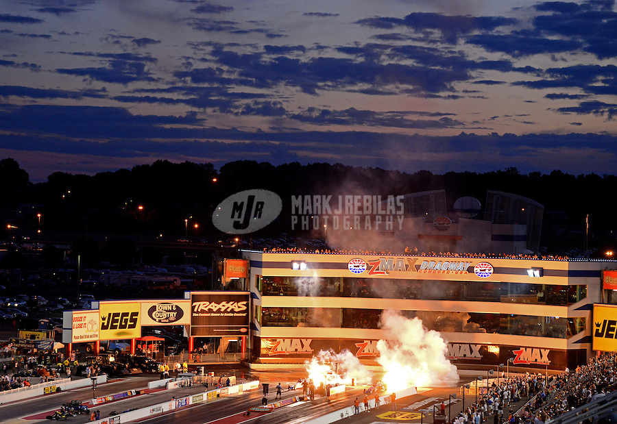 Sept. 14, 2012; Concord, NC, USA: NHRA jet car drivers shoot flames from their cars as the sun sets during qualifying for the O'Reilly Auto Parts Nationals at zMax Dragway. Mandatory Credit: Mark J. Rebilas-