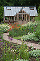 Greenhouse and garden, early June. Planting includes Anthemis tinctoria 'Sauce Hollandaise', Geum 'Fire Opal', and Camassia leichtlinii 'Alba'.