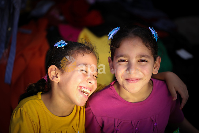 Riham and Hanin Zidan, 8-year-old, a Palestinian twins pose for a photograph as they help their father in his work at a street market in al-Shati refugee camp, western Gaza City, Aug 12, 2013. The mother of Riham and Hanin faced a hard time conceiving a baby for a 15 years of marriage before they are born naturaly. Photo by Mahmoud Hamda