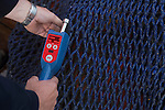 Commercial fisherman measuring net mesh size
