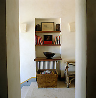 Wooden shelves in a simple alcove on the staircase landing with a floor of untreated travertine