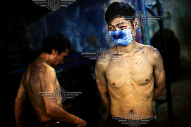 """A textile worker wearing a face mask takes a break at dawn after scrubbing jeans all night using a sanding machine at a garment factory. The blue dust from the jeans is a heavy irritant to the lungs. The factory, which specifically carries out a wear-and-tear process used to achieve a fashionable distressed look, produces approximately 10,000 pairs of jeans every day. Thousands of workers labour through the night scrubbing, spraying and tearing jeans in order to meet the production demand. The factory is owned by Huang Dehong, who left his impoverished village and arrived penniless in Zhongshan twenty years ago. China, the """"factory of the world"""", is now one of the world's largest producers of jeans and its textile workers are among the 200 million migrant labourers criss-crossing the country looking for a better life..."""