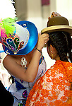 Young Bolivian cholita gets help with her hat from a participant in the Independence Day festivities in La Paz, Bolivia.