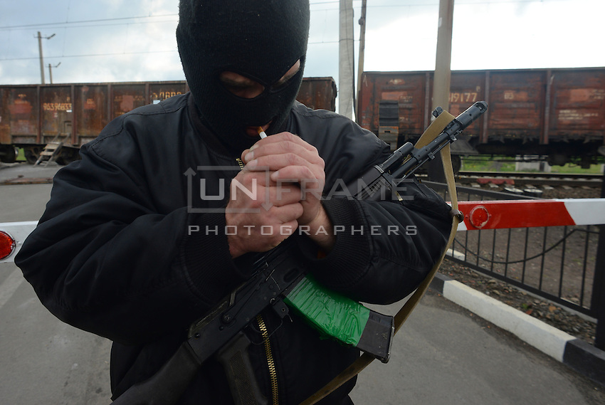 A hooded Pro-Russian soldier lights a cigarette hlding a machine gun at a railroad checkpoint. Slavyansk, Donetsk region.