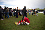 A distraught visiting player slumped on the pitch as home fans celebrate at Key's Park after the Hednesford Town versus FC United of Manchester Northern Premier League premier division play-off final. The match would decide which club were promoted to the Blue Square Conference North. Hednesford won the game by 2 goals to 1 in front of a stadium record attendance of 4412 spectators.