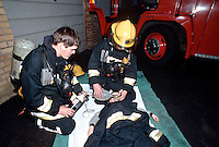 Firefighters in breathing apparatus. On their tunics are  right angled intrinsically safe torchs. There are also  A.D.S.U., an automatic distress signialling unit, which is part of their B.A. sets. This unit emits a very loud whistle should the firefighters remain motionless for a short period. Therefore, if they are trapped the unit will sound and will allow other firefighters to locate them. They have just rescued a young child from a first floor bedroom house fire. The fire had taken control of building and the firefighters were searching in temperatures in excess of 1000 degrees centigrade. They have placed the child on a blanket and are giving him oxygen because he has suffered smoke inhalation. ..© SHOUT. THIS PICTURE MUST ONLY BE USED TO ILLUSTRATE THE EMERGENCY SERVICES IN A POSITIVE MANNER. CONTACT JOHN CALLAN. Exact date unknown.john@shoutpictures.com.www.shoutpictures.com.
