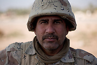 Iraqi tank gunner Hammed Dhamin from the 1st company, 1st armour battalion of the 1st mechanized Iraqi Army Brigade  while conducting  patrols, check points and observation posts on code name route Michigan, the main road of Ramadi in the week during the national election on WED Dec 14 2005 in Ramadi, Iraq. 1st company is part of the first armor battalion of the New Iraqi Army. it has started its training in January 2005. after 50 days their 35 russian and chinese built T 55 tanks begun conducting operations under the guidance of a US military adivisor team. in April 2005 they patrolled in the Abu Ghraib area concluding their first significant mission. While these old tanks are rolling on the ramadi streets more modern T72s are getting ready to become fully operational in Taji, their main base. the Iraqi army wanted to show their power in ramadi during the Dec 15 elections displaying their new armour company. but like all the other Iraqi forces they are not going to secure the polling sites, staying in the rear with the rest of the iraqi and coalition forces. T 55s are very old tanks. production begun in the late 50s to the late 70s. athough obsolete many countries still use the T55 as their main heavy armoured combat vehicle. slow, heavvy and with very little room for the crew it suffers from many mechanical problems constantly challenging the iraqi mechanics and engineers.
