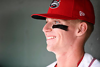Designated hitter Brett Netzer (12) of the Greenville Drive sits in the dugout prior to a game against the Asheville Tourists on Wednesday, August 2, 2017, at Fluor Field at the West End in Greenville, South Carolina. Greenville won, 1-0. (Tom Priddy/Four Seam Images)