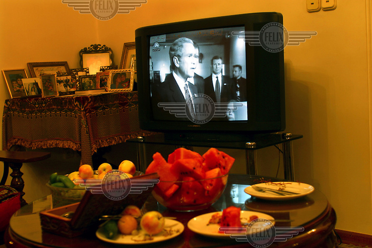 President George W. Bush appears on a satelite TV  programme broadcast from Los Angeles and illegally received by a household in Tehran. This and similar channels, run by exiled Iranians, are highly critical of the regime and promote dissent within Iran. The programming promotes connections with the U.S. and the West, and some endorse the return to power of the son of the former Shah of Iran's son, Reza Pahlavi.