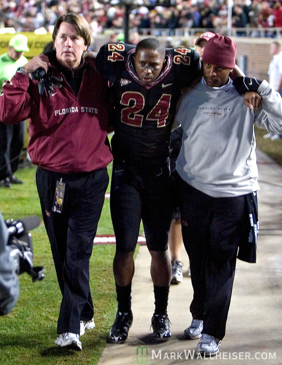 FSU safety Darius McClure is helped to the dressing room after intercepting Boston College late in the 2nd half of Florida State's 27-17 loss to Boston College at Bobby Bowden field on the Florida State University campus in Tallahassee, Florida November 15, 2008.  (Mark Wallheiser/TallahasseeStock.com)