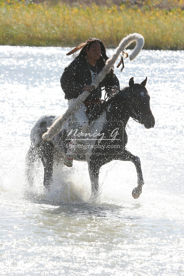 A Native American Sioux Indian on horseback crossing a river in South Dakota