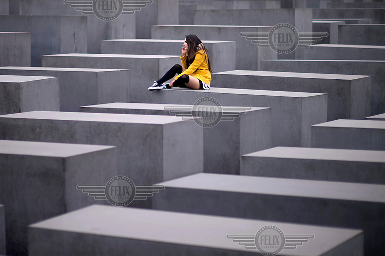 A young woman talks on a phone as she sits on one of the stelae that form the Holocaust Memorial.