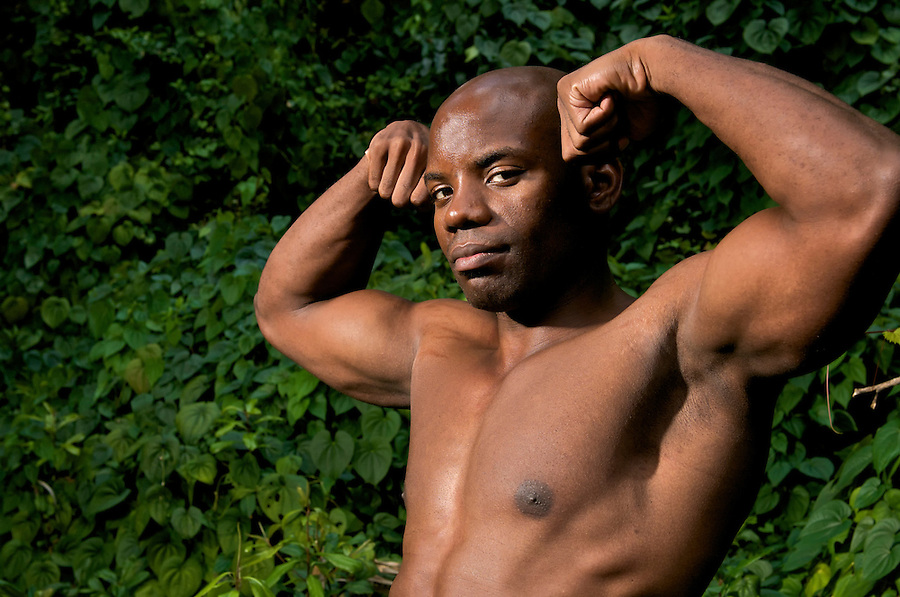 Bodybuilder african american poses in natural environment after an exercise routine.