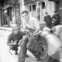 American officer and French partisan crouch behind an auto during a street fight in a French city, ca.  1944. (Army)<br /> Exact Date Shot Unknown<br /> NARA FILE #:  111-SC-217401<br /> WAR & CONFLICT BOOK #:  1055