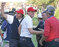 28 SEP 12  Phil Mickelson salutes the fans as Keegan and Mark Bradley  celebrate on the 17th green at the conclusion of their 2-up victory over McIlroy and McDowell at Fridays four ball matches  at The 39th Ryder Cup at The Medinah Country Club in Medinah, Illinois.