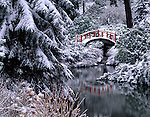 Seattle, WA           <br /> Red foot bridge and reflecting pond after heavy winter snow; Kubota Gardens