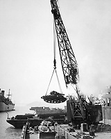 Marine Corps tanks - ready for the front lines - are swung aboard a barge at the Naval Supply Center by crane, for transhipment to our forces in the Pacific Far Eastern Command.  Oakland, CA, 1950.  Acme. (USIA)<br /> Exact Date Shot Unknown<br /> NARA FILE #:  306-PS-50-12226<br /> WAR & CONFLICT BOOK #:  1403