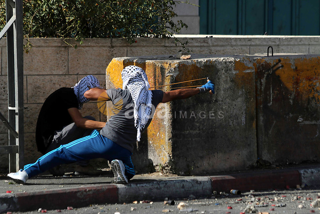 A Palestinian protester uses a sling to throw stones at Israeli troops during clashes in the West Bank city of Bethlehem October 14, 2015. Seven Israelis and 30 Palestinians, including children and assailants, have been killed in two weeks of bloodshed in Israel, Jerusalem and the occupied West Bank. The violence has been partly triggered by Palestinians' anger over what they see as increased Jewish encroachment on Jerusalem's Al-Aqsa mosque compound. Photo by Muhesen Amren