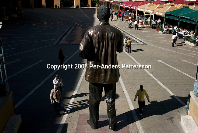 SANDTON, SOUTH AFRICA - JUNE 22:  Shoppers visit the Nelson Mandela Square on June 22, 2008 in Sandton, South Africa. It is an exclusive shopping mall, and has many good restaurants, hotels and offices for financial companies. A huge 20-foot bronze statue of Nelson Mandela is standing in the square. Every day tourists come there to touch it and have their picture taken next to it. (Photo by: Per-Anders Pettersson/Getty Images)..