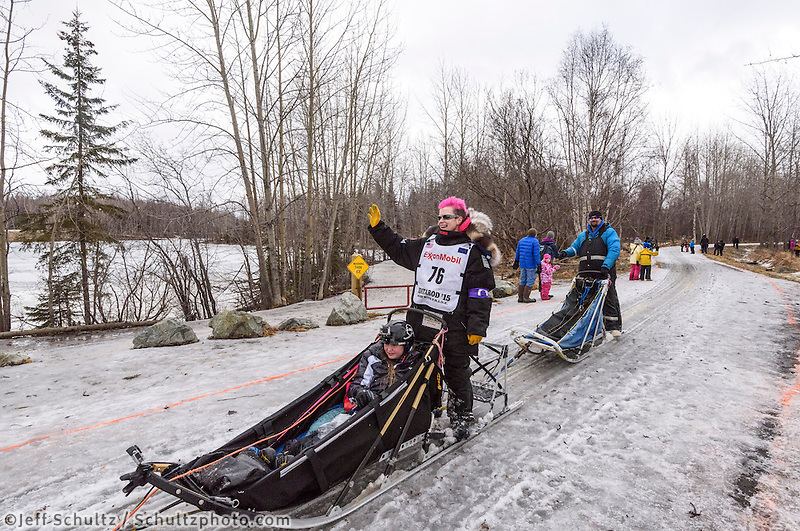 Heidi Sutter and team run past spectators on the bike/ski trail with an Iditarider in the basket during the Anchorage, Alaska ceremonial start of the 2015 Iditarod race. Photo by Ed Bennett/IditarodPhotos.com