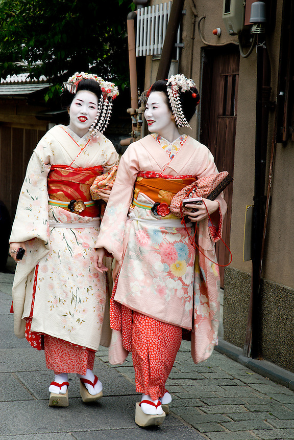 Two beautiful Japanese tourists walk the cobbled streets of the old geisha district of Gion dressed as maiko, or apprentice geisha, Kyoto, Japan.