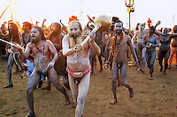 "India. Uttar Pradesh state. Allahabad. Maha Kumbh Mela. Royal bath on Mauni Amavasya Snan (Dark moon). The ritual ""Royal Bath"" is timed to match an auspicious planetary alignment, when believers say spiritual energy flows to earth. Naga (naked) Sadhus celebrate their joy after taking a dip in Sangam and worship the river Ganges. The Naga Sadhus have their bodies smeared with ashes. They were once warriors, that's why they still carry weapons, such as Gada, Trishula with Dumroo and Swords. A gada is an Indian legendary martial art weapon that uses a heavy head on the end of a handle to deliver powerful blows. It typically consists of a single strong, heavy metal shaft featuring a ball-shaped head made of metal. The head is used to strike the opponent by holding the shaft. The gada is the main weapon of the Hindu God Hanuman, an avatar (incarnation) of Shiva. A trishula is a type of Indian trident, commonly used as a Hindu religious symbol. The word means ""three spear"" in Sanskrit. In India, the term often refers to a short-handled weapon which may be mounted on a danda or staff. The trishula is wielded by the Hindu God Shiva. Dumroo is probably the oldest and traditional form of percussion instrument in India. It is most commonly known for its association with Lord Shiva. The sword is the weapon of Kali who is the Hindu goddess associated with empowerment. The Kumbh Mela, believed to be the largest religious gathering is held every 12 years on the banks of the 'Sangam'- the confluence of the holy rivers Ganga, Yamuna and the mythical Saraswati. 10.02.13 © 2013 Didier Ruef"