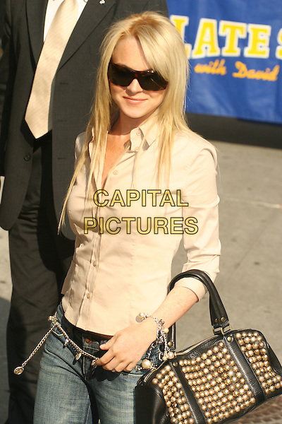 LINDSAY LOHAN.at ''The Late Show with David Letterman''.Ed Sullivan Theatre,.New York City, NY, USA,.June 21, 2005..half length black sunglasses beige cream shirt studded bag gold studs beads bracelet belt.Ref: IW.www.capitalpictures.com.sales@capitalpictures.com.©Ian Wilson/Capital Pictures.