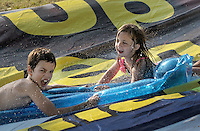 NWA Democrat-Gazette/BEN GOFF &bull; @NWABENGOFF<br /> Children take a ride down a roughly 150 yard waterslide on Saturday Aug. 1, 2015 at the home of Hutch Kufahl in Bentonville. Kufahl, youth pastor at First Baptist Church of Bentonville, organized the waterside as an activity for his Studio 412 high school youth group.