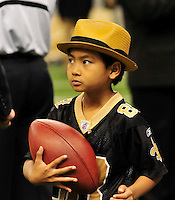 """NFL Saints -Maddox plays with a football the the Saints gave him before the NFC playoff game.Actor Brad Pitt and his adopted son Maddox, Maddox looks at Brads blackberry after Brad took his photo and then they sent it to his mom Angelina Jolie while on the sidelines before teh game. walk on the New Orleans Saints side line before the NFC playoff game between the Saints and the Cardinals Saturday jan. 16, 2010 in Louisiana at the SuperDome. Brad has been instrumental in rebuilding the lower ninth ward in New Orleans through his Make it Right non profit that is building """"green homes"""" where Hurricane Katrina destroyed everything. The Saints beat the Cardinals to advance in the playoffs. Photo ©Suzi Altman/Suzisnaps.comNFL Saints -Cardinals playoffs. Photo ©Suzi Altman/Suzisnaps.comNFL Saints -Cardinals playoffs. Photo ©Suzi Altman/Suzisnaps.com"""