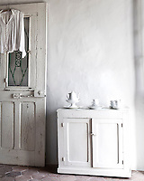 A rustic white painted cupboard in the bedroom displays a collection of fine porcelain