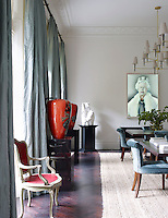 The dining room is furnished with custom-made velvet chairs around a pair of square tables