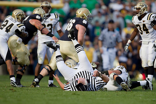 Umpire Bruce Palmer gets knocked down as Western Michigan defenders make tackle during NCAA football game between Western Michigan and Notre Dame.  The Notre Dame Fighting Irish defeated the Western Michigan Broncos 44-20 in game at Notre Dame Stadium in South Bend, Indiana.