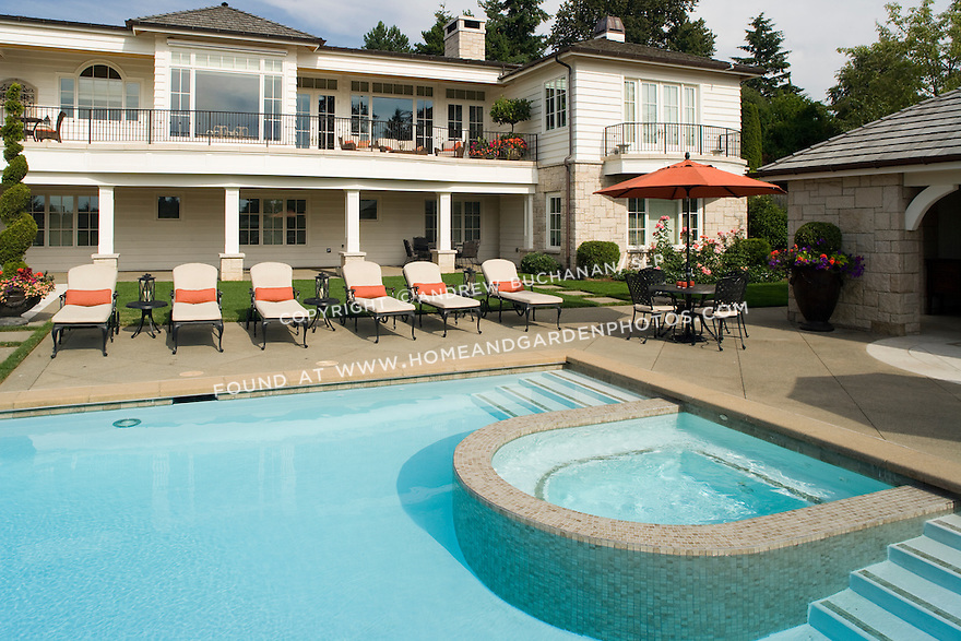A sunny, summer afternoon scene in suburban Seattle showing a beautifully landscaped yard and swimming pool patio including six identical lounge chairs with matching orange red cushions and a built in tiled spa.