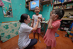 Nirish Camporedondo, a student in the Mary Johnston College of Nursing in Manila, helps 5-year old Jean Jamilla Tulauan (center) and her 4-year old sister Jewell Rae hear their heartbeats during a visit to the girls' home in the Parola neighborhood of Manila's Tondo section. Camporedondo and other nursing students regularly visit the neighborhood to do health education and monitor the health of residents. The students also run a feeding program for neighborhood children.<br /> <br /> The nursing school is supported by United Methodist Women.
