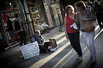 """A man begging on the streets of Madrid with a sign that says """" I have not work """""""