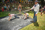 Independence Day celebration Main Street, Mokelumne Hill, California..Kids enjoy sliding in the water on a sheet of plastic in the park.