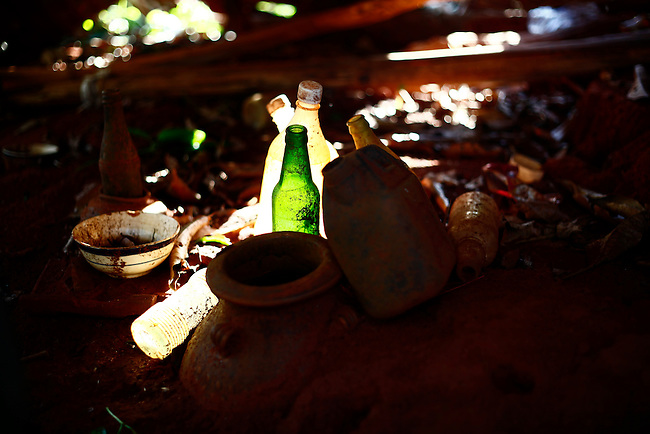 The late afternoon sun illuminates several glass bottles and other items left as offerings inside a tomb at a Jarai cemetery in the Central Highlands near Kon Tum, Vietnam. The Jarai are the largest of more than two dozen Montagnard, or Dega, hill tribes. They believe the spirits of the deceased linger for a long time, often years, after death, and they build a small house over the grave so the spirit will have somewhere to live. Offerings of food and drink and other items are left inside to appease the spirit before it moves on to the next world. April 14, 2012.