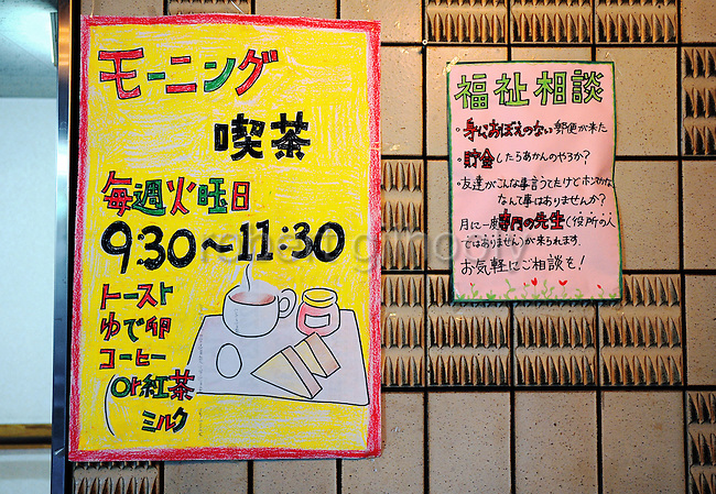 Signs advertising morning breakfast and advice on social welfare issues are displayed at the entrance to a shelter that was once a hotel in the Kamagasaki district of Osaka, Japan. Several hotels in the area have been converted into low-cost accommodations for elderly people who were formerly unemployed and/or homeless..
