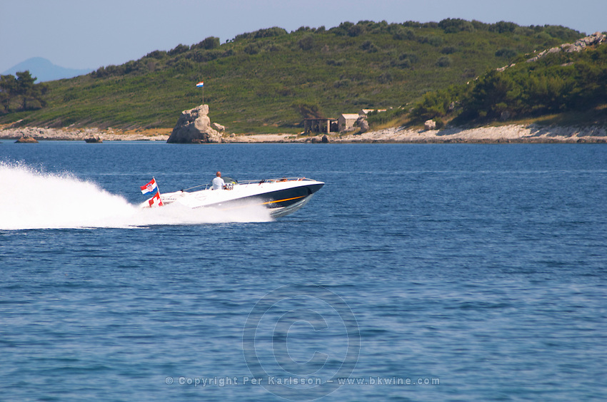 A speedboat speed boat in high speed across the water with white spray with the Croatian and Swiss flags and an island in the background Orebic town, holiday resort on the south coast of the Peljesac peninsula. Orebic town. Peljesac peninsula. Dalmatian Coast, Croatia, Europe.