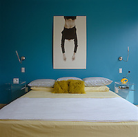 A vibrant blue wall in the master bedroom provides a splash of colour in this predominantly white house