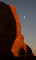 A rising moon appears over the landscape at Arches National Park, Utah