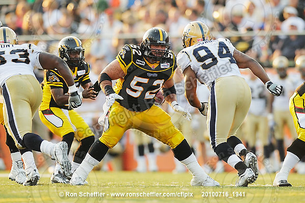 July 16, 2010; Hamilton, Ontario, Canada; Hamilton Tiger-Cats offensive lineman George Hudson (52) moves to block Winnipeg Blue Bombers defensive lineman Deji Oduwole (94). CFL football: Winnipeg Blue Bombers vs. Hamilton Tiger-Cats at Ivor Wynne Stadium. The Tiger-Cats defeated the Blue Bombers 28-7. Mandatory Credit: Ron Scheffler. Copyright (c) 2010 Ron Scheffler.