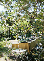 Surrounded by olive trees a table is laid for lunch in the garden