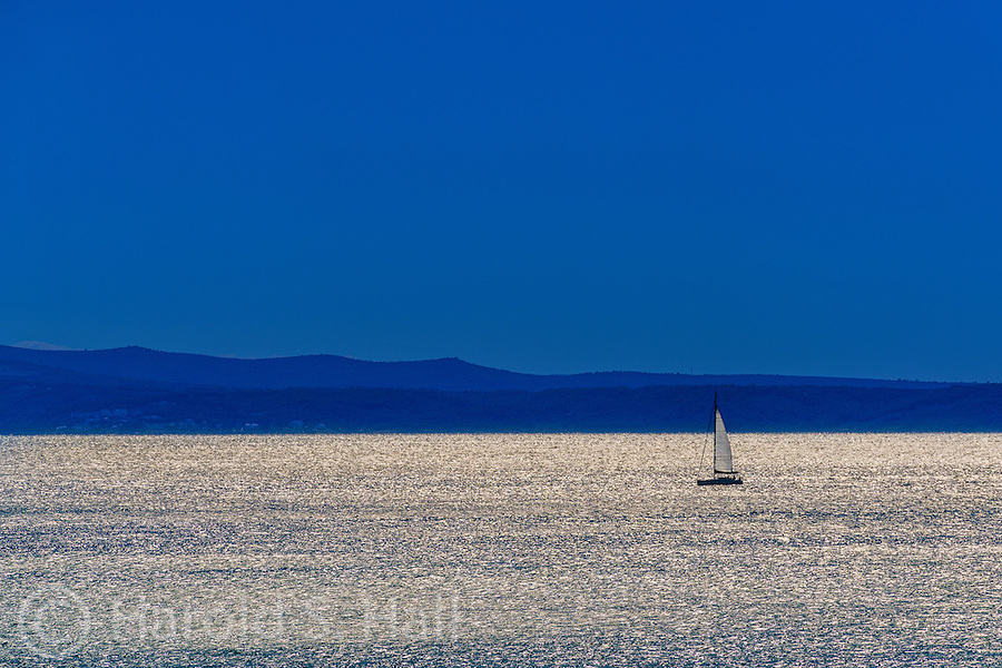 A lone sail boat sails late into the evening with a full moon above.