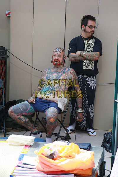 ATMOSPHERE.The London International Tattoo Convention in east London, Tobacco Dock, England..September 27th, 2009.gv general view tattoos ink full length topless sitting .CAP/MAR.© Martin Harris/Capital Pictures.