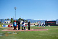 The umpires and Inland Empire 66ers stand in the field during the singing of the National Anthem before a California League game between the Modesto Nuts and the 66ers on April 10, 2019 at San Manuel Stadium in San Bernardino, California. Inland Empire defeated Modesto 5-4 in 13 innings. (Zachary Lucy/Four Seam Images)