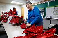 NWA Democrat-Gazette/DAVID GOTTSCHALK Patsy Christie, planning director for the city of Springdale, makes red bows Thursday, November 8, 2018, for decorative Christmas baskets at the City Administration Building in Springdale. The handmade baskets will be hung on 22  lamp posts on Emma Avenue in downtown Springdale.