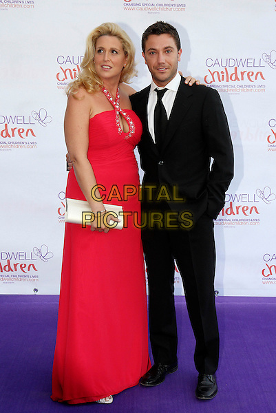 JESSICA & GINO D'ACAMPO.The Caudwell Children Butterfly Ball at Battersea Evolution, London, England..May 20th, 2010 .full length red halterneck maxi dress black suit  married husband wife silver clutch bag .CAP/MAR.© Martin Harris/Capital Pictures.