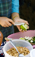 Woman slicing lime in preparation of Hmong cuisine.  Hmong Sports Festival McMurray Field St Paul Minnesota USA