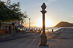 People enjoying sunset at cafes by the harbour - Memorial statue in silhouette.